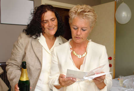 lesbianism: Just married mature lesbian couple reading congratulations card at their wedding party. Same- marriage is legal and official in Belgium. Stock Photo