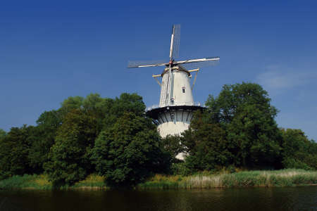 airstream: A traditional and typical Dutch windmill on the salient angle of a bastion (now a park) in the old city of Middelburg in The Netherlands. Wet ditch in front of the windmill and shrubs-covered bastion. Stock Photo