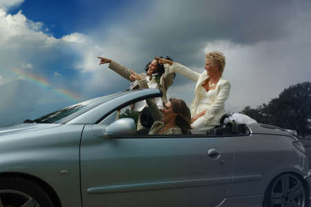 bigotry: Mixed-age group of women pointing to a bright future in a convertible sports-car. Concept of liberation and escape from bigotry. Concept of feminism, gay and lesbian pride, and diversity.