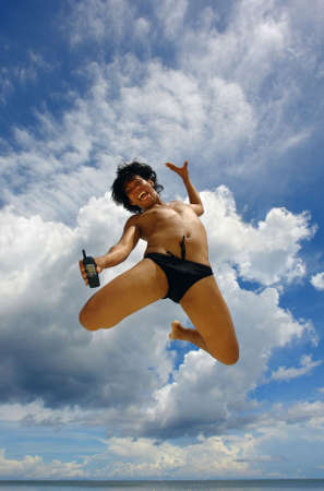 Sky-high jump showing cell phone by Asian boy in the tropics, advertising a new brand of cell phone or cell phone subscription service. Concept of success, soaring, enthusiasm, sales. Marketing an outstanding product. Empty room on cell phone and in the s photo