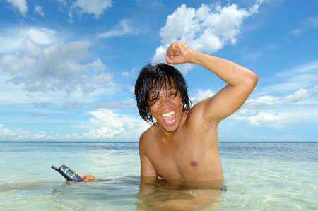 enthusiasm: Asian boy in a tropical sea advertising a semi-submerged cell-phone under a majestic cloud-scape. Concept of enthusiasm and sales for an unusual service. Marketing an outstanding product. Empty room on cell phone and in the sky to add own text.