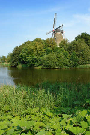 A traditional and typical Dutch windmill on the salient angle of a bastion (now a park) in the old city of Middelburg in The Netherlands. Wet ditch and embankment in front of the windmill and shrubs-covered bastion.