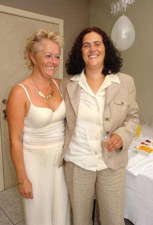 レズビアンの成熟したカップルのポーズと彼らの結婚式でシャンパンを祝うパーティーの公式の結婚式の後。同じ結婚はベルギーで完全に合法です。