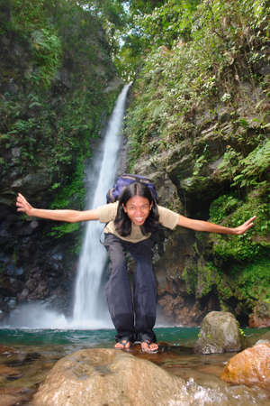 Asian exotic longhaired boy in front of a tropical pristine waterfall, performing flying poses and movements. photo