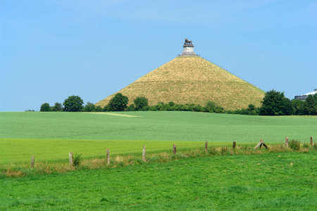 defeated: The famous memorial hill on the battlefield in the rolling countryside of Waterloo, Belgium, where the French emperor Napoleon was defeated decisively by an alliance of English, German, Prussians and Dutch in 1815, ending 20 years of French expansionism i Stock Photo
