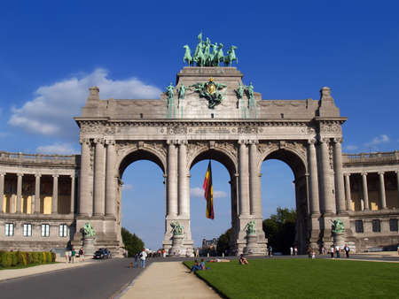 Triumphal arch in the Parc du Cinquantenaire, Brussels. A landmark to commemorate Belgium's half-centennial independence. Sunny Sunday afternoon, city people at strolling and relaxing at leisure.