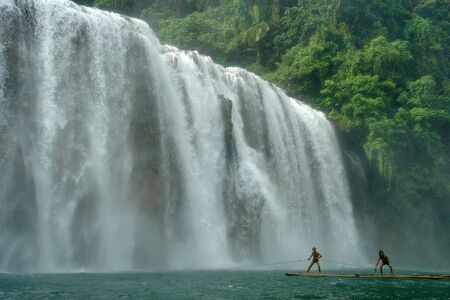 The wide cascading Tinuy-an waterfalls near Bislig city, Mindanao, Philippines, called the Niagara of the Philippines, in a pristine virgin rain-forest setting. Two boys playing on a raft in front.