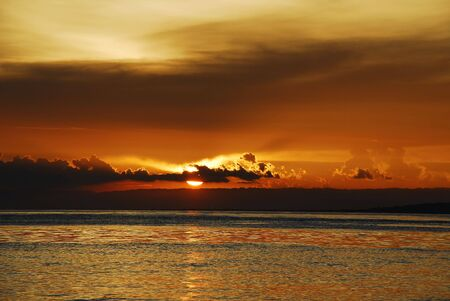 Chocolate-coffee colored flamboyant sunset on a tropical exotic beach with golden reflections in the sea and mountains in the background.