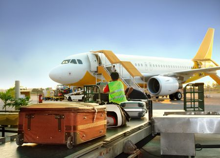 Luggage handling on airport: transfer from cart to the luggage carousel with airplane and cargo loading in the background and detail of suitcases. Zdjęcie Seryjne