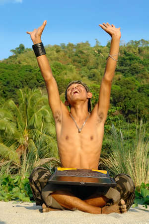 Asian young soldier or terrorist sitting in an exotic jungle with laptop PC and making a triumphant cheering gesture with arms high up. Concept of victory and success. photo