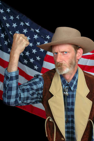 superiority: Senior US patriot in traditional Western outfit making a threatening fist and claiming superiority and supremacy backed by the stars and stripes American flag. Stock Photo