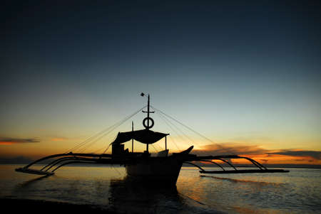 fishermens: Asian fishermens boat anchored on a beach in a colorful tropical sunset. Stock Photo