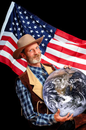 superiority: Senior US patriot in traditional Western outfit holding the globe and claiming ownership of it, and superiority and supremacy backed by the stars and stripes American flag.
