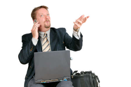 travelling salesman: Traveling bussinesman, sitting in a waiting shed on an airport or train station with luggage and laptop PC, calling the office organizing or explaining. Isolated over white.