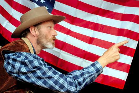 superiority: Senior EE.UU. patriota en traje tradicional occidental que apunta y amenaza para asustar a los invasores fuera, alegando la superioridad de propiedad y el respaldo de las estrellas y franjas bandera americana.