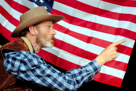 trespasser: Senior US patriot in traditional Western outfit pointing and threatening to scare off invaders, claiming superiority and property backed by the stars and stripes American flag.