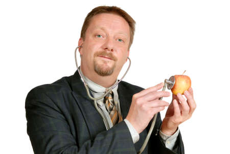 Alimentación de salud inspector examina una manzana con un estetoscopio. Metáfora de control de la calidad de los alimentos. Aislado en blanco.