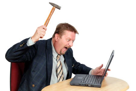 Frustrated user or businessman in his office threatening to destroy his PC with a hammer out of sheer frustration for malfunctions, faulty or over-complicated software design or bad usability. Isolated over white. Stock Photo