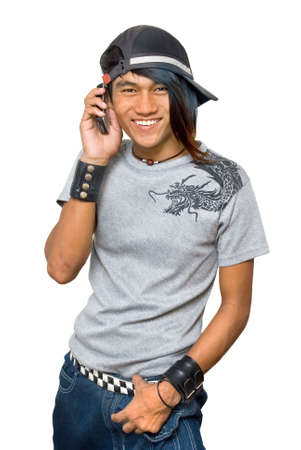 Asian teenager with cap and cell phone, calling and smiling, and with punk one-sided colored long hair. Emo and friendly macho punker boy. Isolated over white. Zdjęcie Seryjne