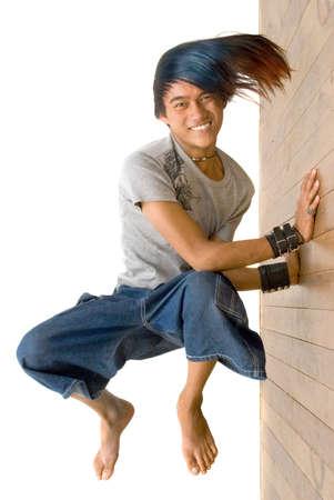 ビジネスやマーケティングのプッシュの制限、精力的な努力、努力、達成および成功のメタファー。アジアの 10 代の少年 break-dancer 笑みを浮かべて、応援は壁に対して押します。白で隔離されました。