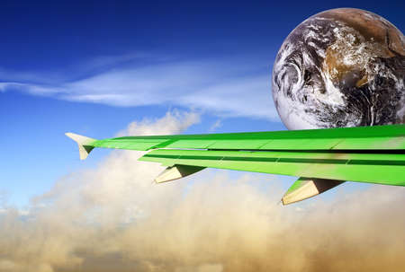 Globe with green airplane wing flying over a tropical cloudscape. Metaphor or concept of energy conservation and more efficient flying in the aviation industry to save energy and reduce CO2 output in order to combat global warming. photo