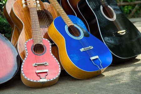 A series of colorful Cebu handmade and manually crafted painted guitars - of various sizes - aligned outdoors in Cebu City (Philippines) downtown on a street sale.