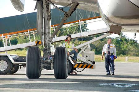 地上の航空会社人員貨物や荷物の商業定期旅客機またはコンベヤー ベルトと主翼ランディングギアの詳細と、駐機場に駐車したジェット機で読み込みを見下ろします。