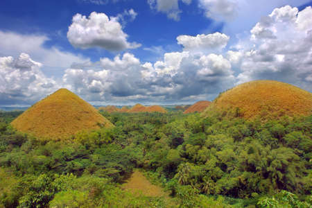 Panorama of the Bohol Chocolate Hills natural landmark, a very prominent and famous tourism geography spot in the Philippines, colorful and under a majestic cloudscape.