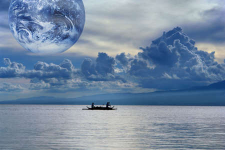 public domain: Blue gloomy sunset on a tropical sea with a cloudscape and globe, and fishermen in a small boat leaving for the nightly catch. Metaphor of water, source of global life on the planet. Globe is public domain photo of NASA. Stock Photo