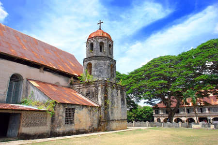 Filipino Catholic Church, bell tower and Convent of St. Isidore Labradore in Lazi on Siquijor Island, built 1857-1884. The Convent is the largest in the Asian area. Church. Bell tower and Covent are a popular tourism landmark and listed in the National Hi Stock Photo - 2511757