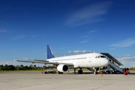 商業定期旅客機は熱帯空港駐機場と紺碧の青空の下で搭乗の乗客と貨物をロード上に駐車。