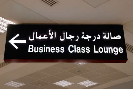 Ceiling sign in Arabic and English in an Arab airport: direction to the business class lounge (Doha, Qatar, code DOH).