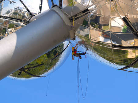 audacious: High-rise construction worker suspended on steel cables working on a modern and daring spherical steel building.