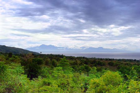 Tropical jungle panorama over a sea strait with mountains and cloudscape in the background. Mt. Bandilaan National Park on Siquijor Island with a view on the Cebu strait and Negros, Philippines.