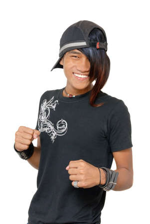 Kung Fu Asian teenager fighter with punk coloured long hairstyle and cap threatening mockingly with his fists. Emo and macho punker boy. Isolated over white.