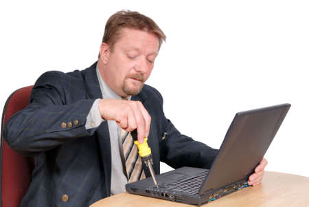 PC technician in a business office opening a laptop computer with a screwdriver for maintenance, to upgrade, to upgrade or repair hardware. Isolated over white.