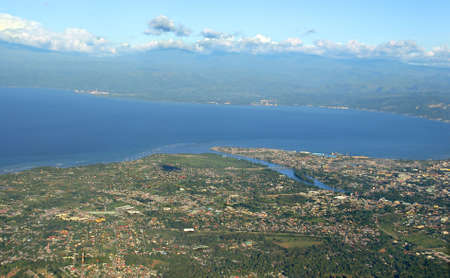 Aerial view of a tropical Asian city with a stream and bridges on a bay, buildings and port. Cagayan de Oro, Mindanao, Philippines.