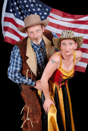 Western senior couple in traditional cowboy outfit in front of an American stars and stripes flag proudly making a dance step and inviting to join. photo