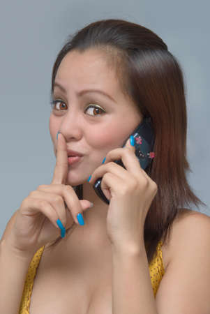 Classy eighteen year old teenage Asian girl portrait, calling by cellphone and making a hushing gesture with index finger as if listening to gossip.