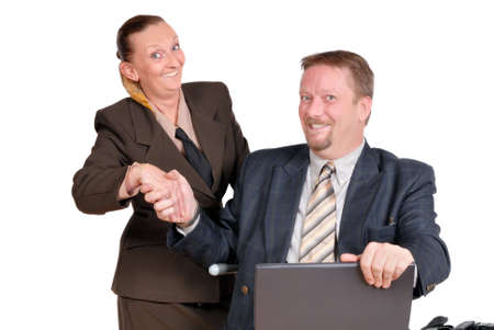 Handshaking travelling businessman and businesswoman in suit and with laptop PC after the successful conclusion of a business deal.