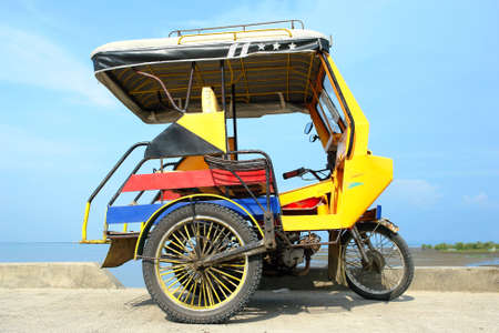 Asian colourful tricycle parked in front of a tropical bay.