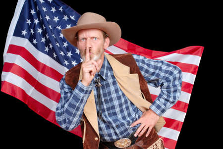 furtive: Hushing senior Western cowboy in traditional outfit in front of an American Stars and Stripes flag.