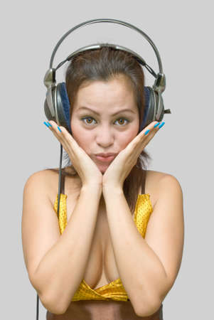 critique: Portrait of eighteen year Asian teen girl with headphones listening to music with a serious facial expression and her hands on her chin.