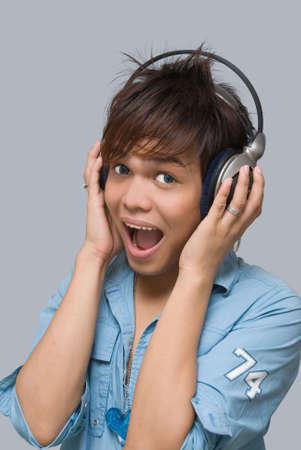 Portrait of eighteen year Asian teen boy with headphones cheering and singing enthusiastically to the sound of music. photo