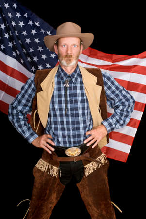 sternly: Firm full-body standing senior cowboy in traditional Western outfit and wardrobe with his hands in his hips peering sternly backed by the stars and stripes American flag.