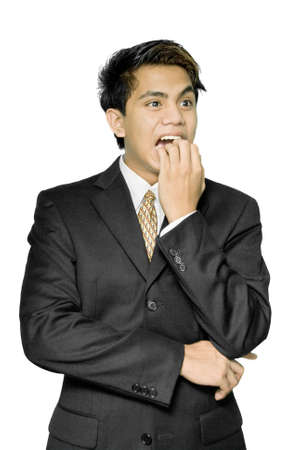 fearing: Young Indian nail-biting and stressed businessman, yuppie type, standing with a terrified overworked expression on his face. Isolated over white. Stock Photo