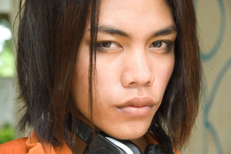 haired: Portrait (tightly cropped on the face) of a slightly effeminate long haired emo or punk South East Asian teenage boy with headset partly visible on a background of a graffiti wall.  Stock Photo