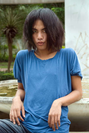southeast asian ethnicity: Long haired emo or punk South East Asian teenage boy sitting outdoors, portrait middle up, with a pouting slightly teasing facial expression. Stock Photo