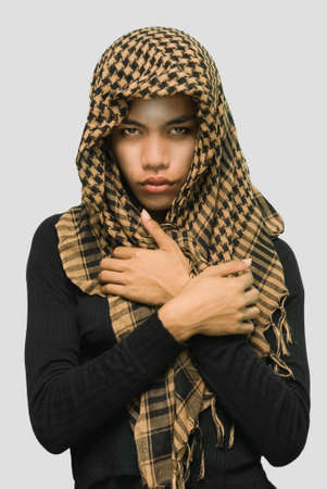 Portrait of Islamic South-East Asian teenage girl in traditional (Bangsomoro, Mindanao, Philippines) dress with headscarf. Isolated over monochrome grey. Caveat: male impersonator. photo