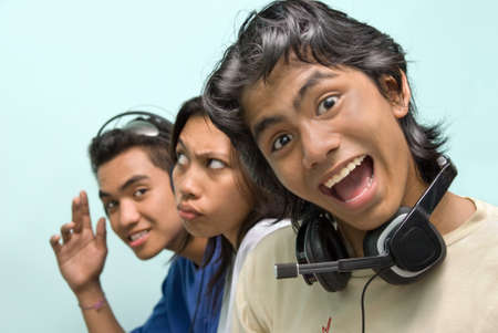 Portrait of three young Asian callcenter, telephone helpdesk or support center agents, faces lined up in a row and with headset, relaxing during break or work time making funny grimaces.